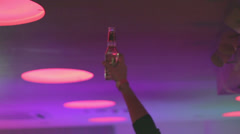 Man holding bottle of beer in nightclub, having party, click for HD Stock Footage