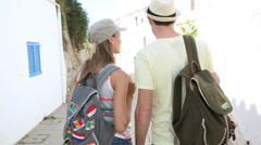 Tourists with backpacks walking in the street of ibiza Stock Footage