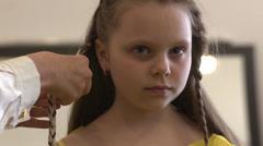 Weaving braids - flower in her hair - stock footage