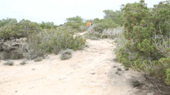 couple riding bikes on island trail - stock footage