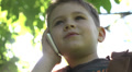 Little boy with no front milk teeth talking on the phone in the park Footage