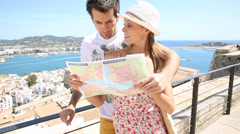 Couple of tourists reading map at the top of ibiza old town Stock Footage