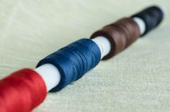a row from coils of threads on a textile background - stock photo