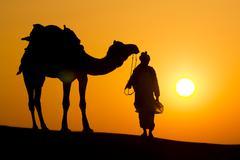 A desert local walks a camel through thar desert Stock Photos