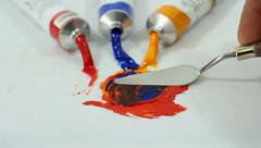 Mixing oil paints with a palette knife. - stock footage