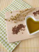 Linseed oil in a small heart-shaped porcelain bowl - stock photo