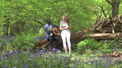 Attractive teenage couple in woods singing and playing guitar (2) Stock Footage