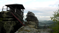 Wooden cabin on main peak of rock as view point, dark clouds in the sky. Stock Footage