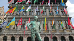 dock labourer statue and flags, antwerp city hall, belgium - stock footage