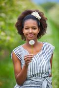 Outdoor portrait of a young beautiful african american woman holding a dandel Stock Photos