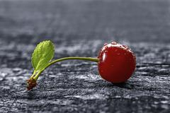 Stock Photo of cherry on wooden table with water drops