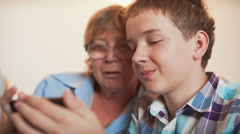 Young boy and old person learn smartphone Stock Footage