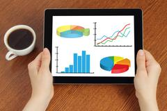 Hands hold tablet pc with graphs . Stock Photos