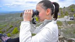 Cute little girl using binoculars on mountain peak, dolly shoot Stock Footage