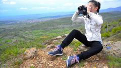 Closeup portrait of a girl looking through binoculars at high mountain peak Stock Footage