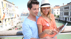 Couple using tablet on the academia bridge in venice, italy Stock Footage