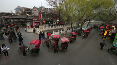 The pedicab drivers and visitors pass over Yinding Bridge at sunset, Beijing Stock Footage