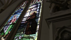 Stained glass window in cathedral with light coming through Stock Footage