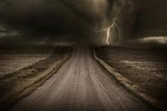 Stormy back country road. heavy storm and lightning bolt in a distans. severe Stock Photos