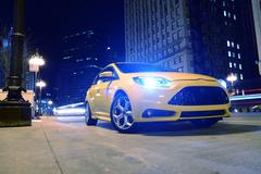 sporty car on the street at night. agressive looking sporty yellow car on the - stock photo