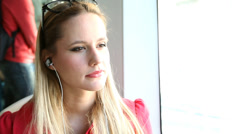 Young beautiful blond woman riding tram, listening to music Stock Footage