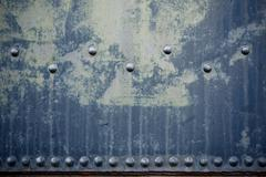 Rusty blue metal background with rivets / bolts. old blue paint. grungy backg Stock Photos