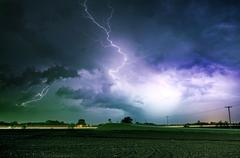 Tornado alley severe storm at night time. severe lightnings above farmlands i Stock Photos