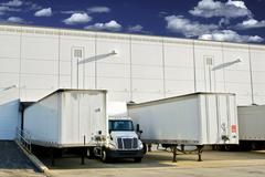 Warehouse loading docks - business district. semi trucks and trailers loading Stock Photos