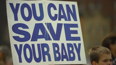 Pro Life Anti Abortion Protestors - Young Boy holding Sign looking sad - stock footage