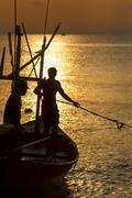 Fisherman silhouette in sea at sunrise Stock Photos