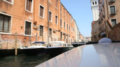 Taxi-boat riding on canal through the island of venice Stock Footage