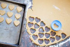 Plastic heart shaped cookie cutter and raw dough cookies on meta Stock Photos