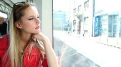 Beautiful young blond woman riding tram, looking out the window Stock Footage