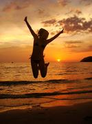 silhouette of young woman jumping at sunset, langkawi island, malaysia - stock photo