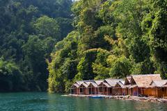 bungalow on tropical lake - stock photo