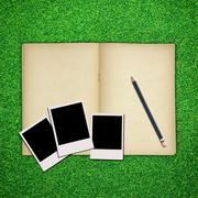 Pencil and photo frame with old book on green grass background Stock Photos