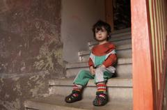 Little boy sitting on stairs Stock Photos