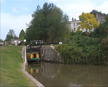 Narrowboat navigates out of a lock on the Kennet and Avon canal near Bath Stock Footage