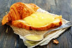 croissant with cream and teaspoon. - stock photo