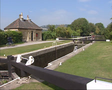 Bath Top Lock on the Kennet and Avon canal, cyclist on towpath + cottage Stock Footage