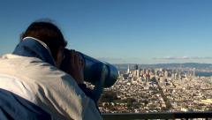 Tourist is looking through a telescopic tower's viewer of San Francisco Stock Footage