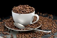 Cup and saucer full of coffee beans with a spoon Stock Photos