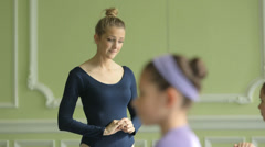 MS Female Ballet Dancer supervises a younger Ballerina and teaches her movements Stock Footage