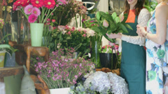 MLS A young Florist advises a woman on a bunch of flowers in the shop - stock footage