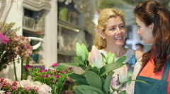 MS A young Florist advises a woman on a bunch of flowers in the shop Stock Footage