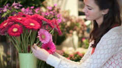 MS A Young woman browses and smells the flowes in their lush array Stock Footage