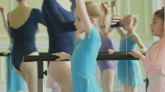 Sliding MS Female Ballet Dancer instructs fouryoung Ballerinas using the barre Stock Footage