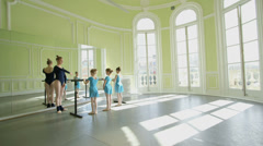 Sliding MLS Female Ballet Dancer instructs three young Ballerinas using the barr Stock Footage