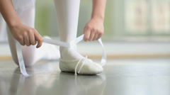 CU A young Ballerina ties the ribbons of her sof top Ballet Shoes Stock Footage
