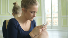 CU Female Ballet Dancer crouches in front of the mirror using smartphone  Stock Footage